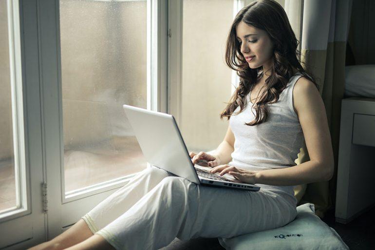 Mujer, computadora y protector solar